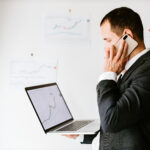 concentrated investment stock broker talking on phone in office